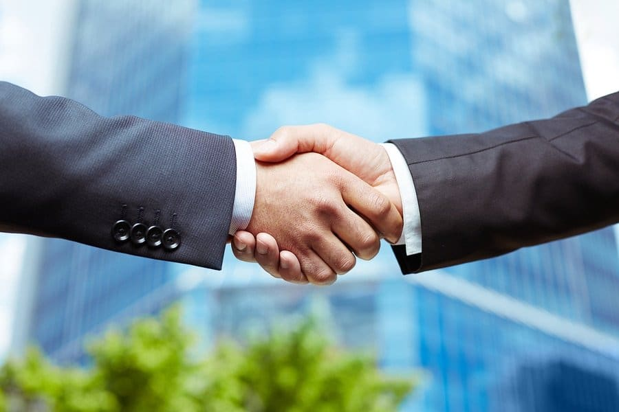 Close-up of business people handshaking on background of modern